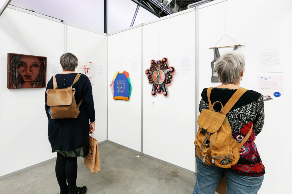 Het geborduurde reisdagboek is geëxposeerd bij het textielplus festival. Twee bezoekers bekijken de inzendingen van de wedstrijd.