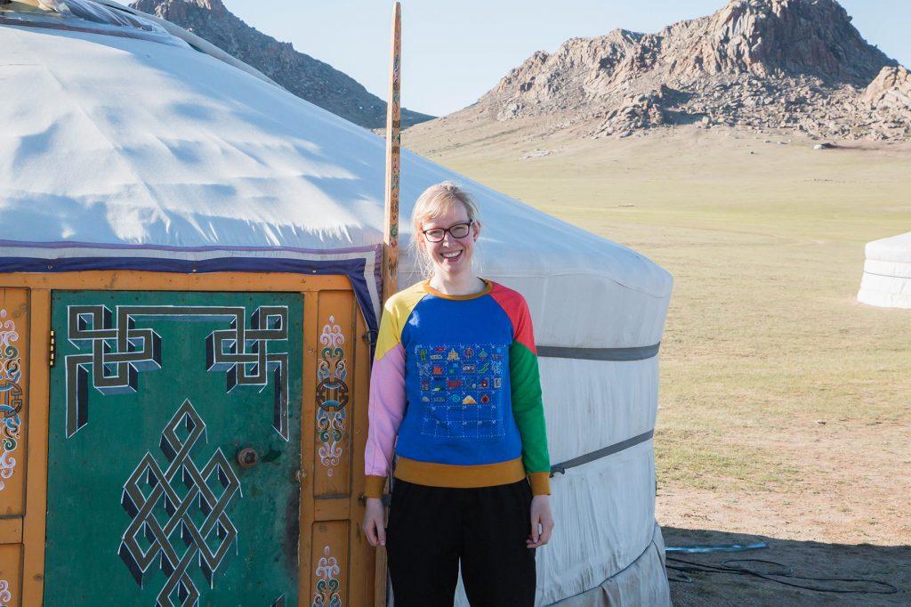 Marjolein Bartels voor een ger in Mongolie, met haar geborduurde reisdagboek trui aan.