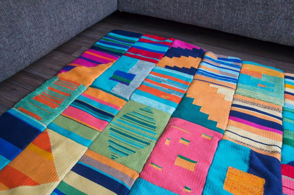 Een kleurrijk vloerkleed, met diverse vlakken en composities.