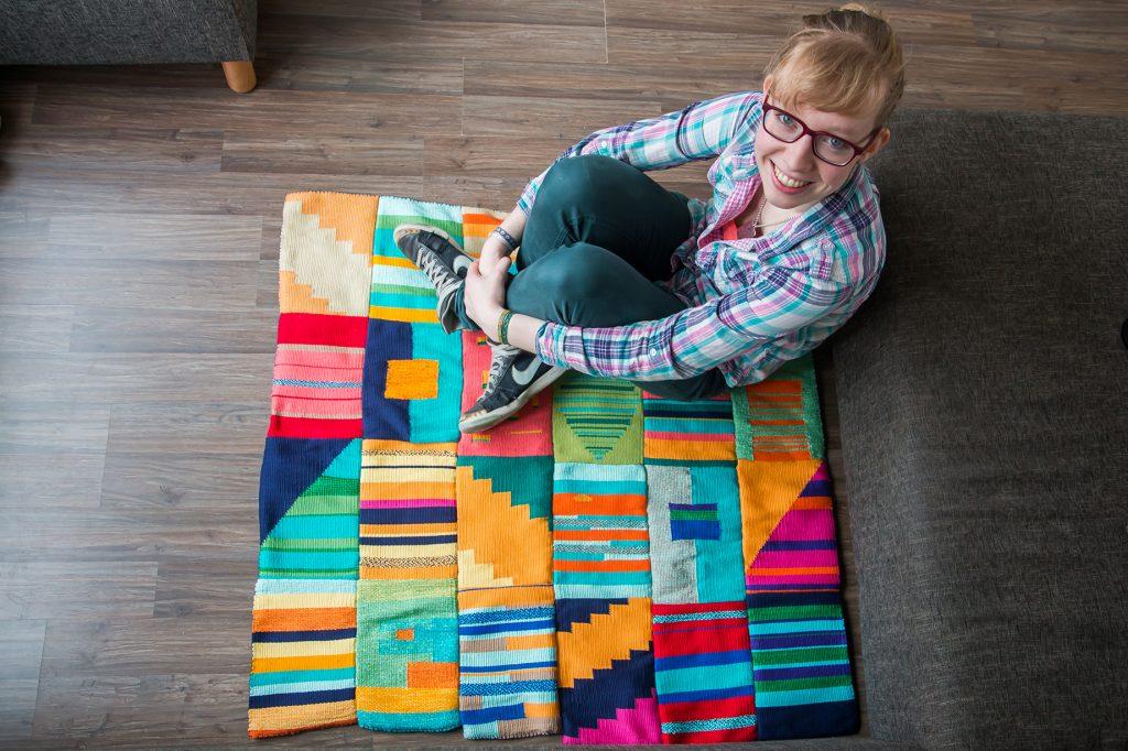Marjolein Bartels zittend op haar geweven vloerkleed. Na het weven heeft ze alle lapjes handmatig aan elkaar genaaid.