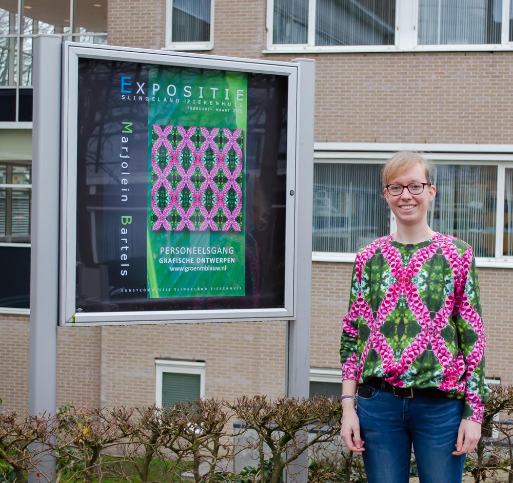 Marjolein Bartels voor het bord met de aankondiging van haar expositie in Ziekenhuis Slingeland Doetinchem.