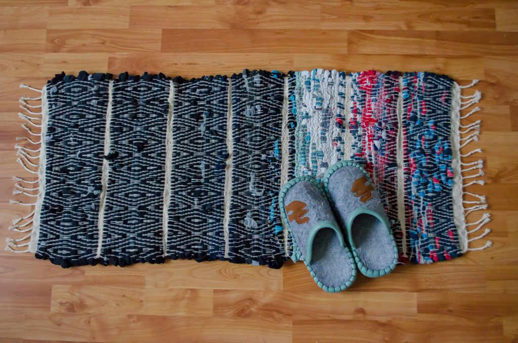 upcycle textiel, handgeweven uniek vloerkleed van oude sokken, met sloffen erop om de verhouding te zien.